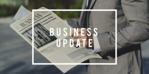 Business Update banner of a businessman in grey suit reading newspaper